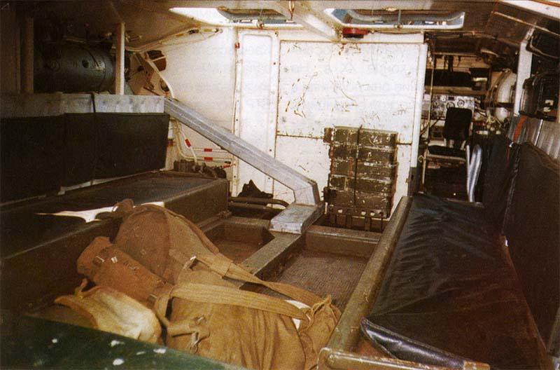 Десантное отделение МТ-ЛБ. Впереди за проходом видно командирское сиденье и радиостанция Р-123М, у стенки двигательного отсека — коробки для пулеметных лент ПКТ, в левом верхнем углу — мощный нагнетатель-отопитель, слева и справа — сиденья для десанта, а под ними «мощные» топливные баки. На переднем плане — солдатские вещмешки стрелков. 27 мсд, п. Тоцкое Оренбургской области, март 2003 г.