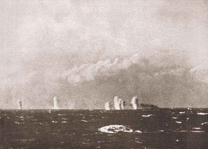 Вид на горящий «Bismarck» с борта британского корабля (черный дым справа). Слева от него видны разрывы от снарядов. 27 мая 1941 г.