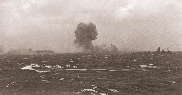 «Rodney» (справа) ведёт огонь по «Bismarck», который горит на горизонте (дым слева). 27 мая 1941 г.