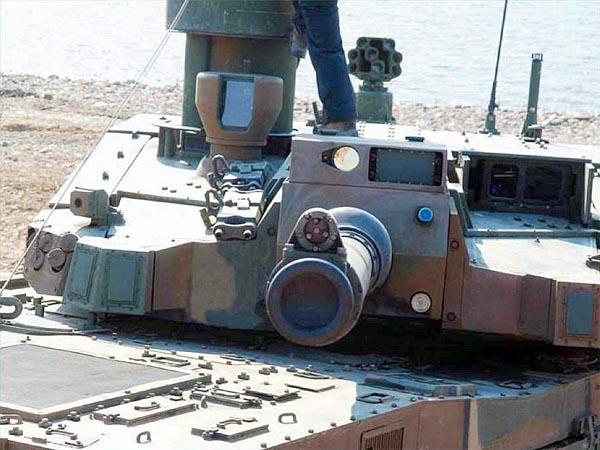 Фронтальный вид на башню танка K2. Хорошо видны командирский панаромический прицел KCPS, прицел наводчика KGPS, зеркало системы контроля кривизны ствола на его дульном срезе, один из датчиков лазерного облучения LWR и другие элементы систем танка
