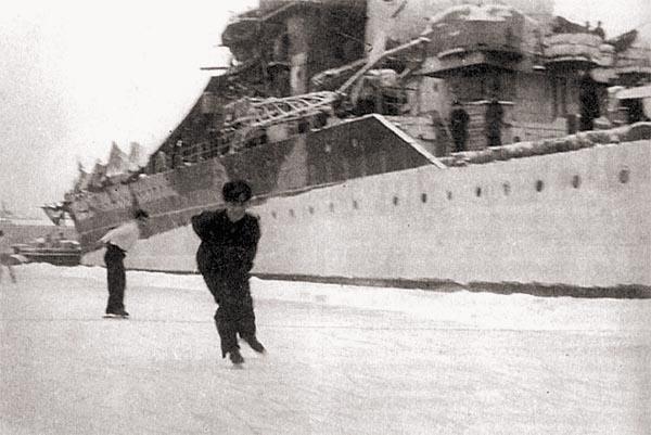 В редкие минуты отдыха: моряки «Кирова» катаются на коньках у борта своего корабля. Обратите внимание на камуфляжную окраску крейсера и укрывающие палубу брезентовые чехлы